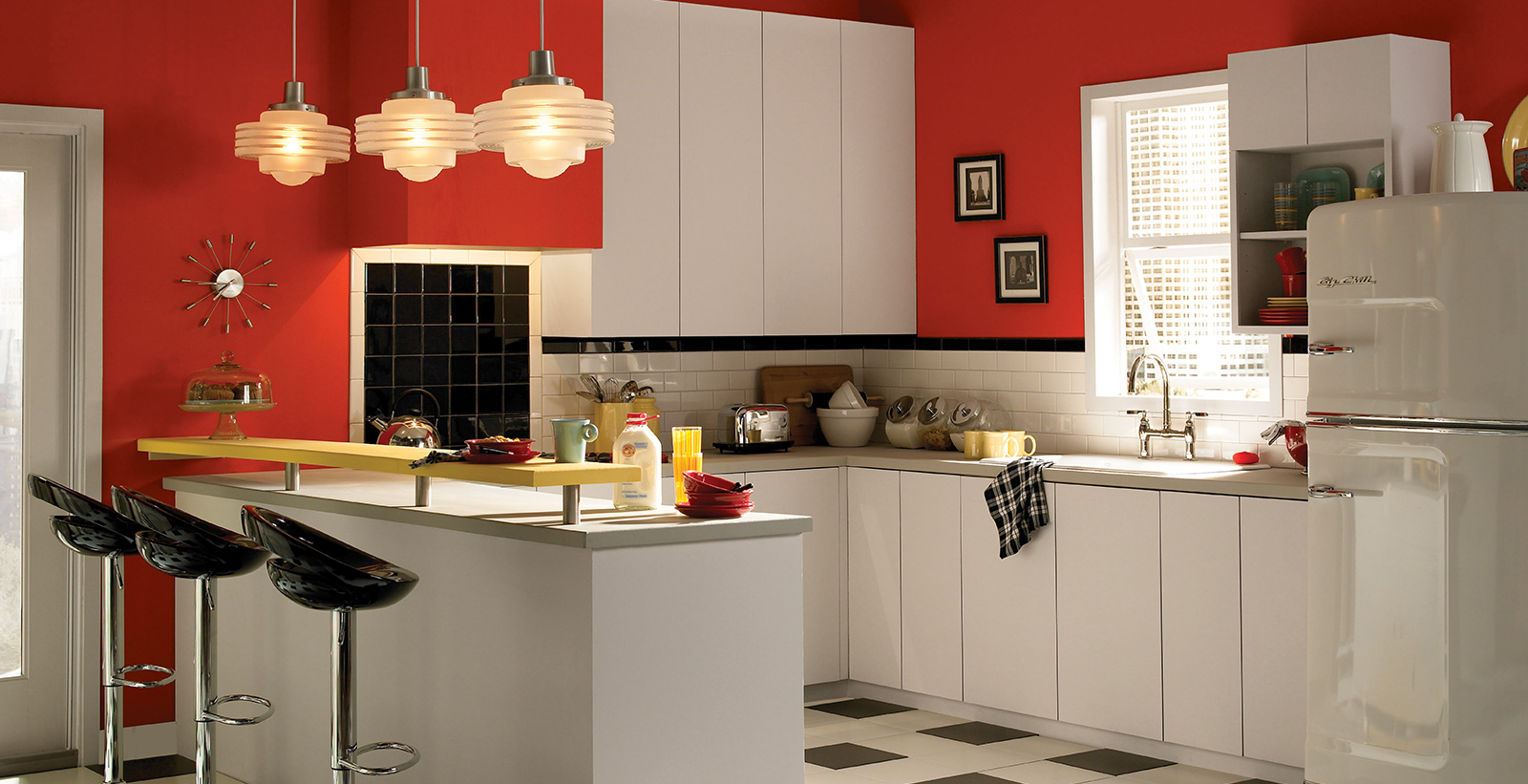 Retro styled kitchen with red on walls, white on cabinets and trim, and white and black checkered flooring