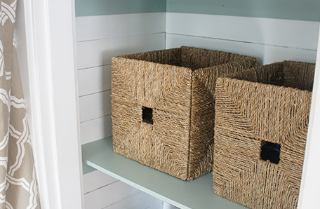 Use wicker baskets for storage on the finished shelves