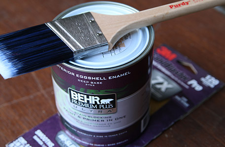 A clean paintbrush, a quart of Behr paint and a sleeve of sandpaper
