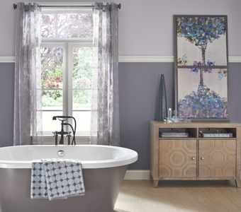 Gray bathroom with stand alone gray bathtub and floral decor.