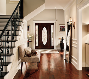 Large entrance with off-white walls, dark wood floors, black stair railings, and black door.
