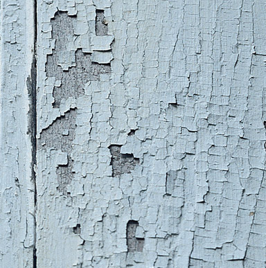Close up image of a surface that has some cracking and flaking paint.