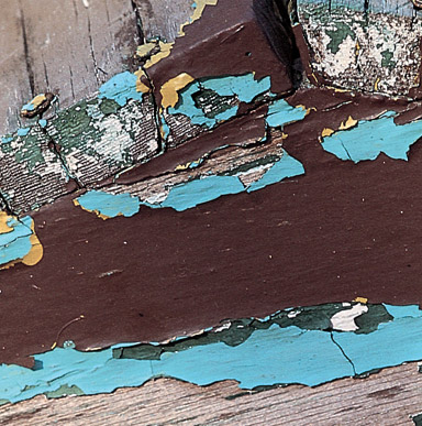 Close up image of a wood with peeling paint and underneath is another coat of a different color.