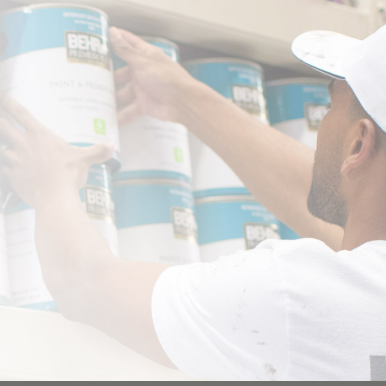 Mobile view of an Image of a Pro Contractor picking up a 1 gallon BEHR paint can at a Home Depot Store rack.