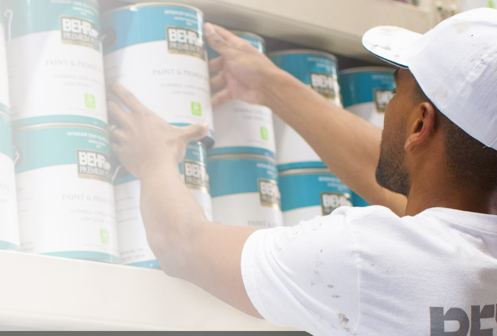 Image of a Pro Contractor picking up a 1 gallon BEHR paint can at a Home Depot Store rack